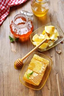 Fresh honey and sliced lemon on wooden table
