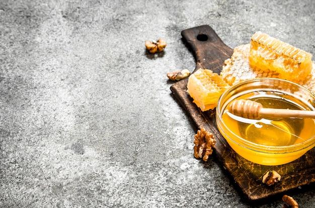 Свежий мед с орехами. на деревенском фоне.