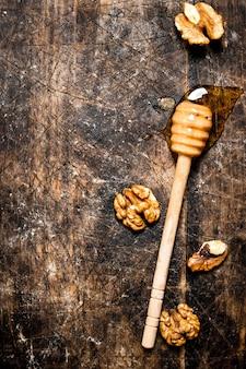 ナッツ入りの新鮮な蜂蜜。木製の背景に。