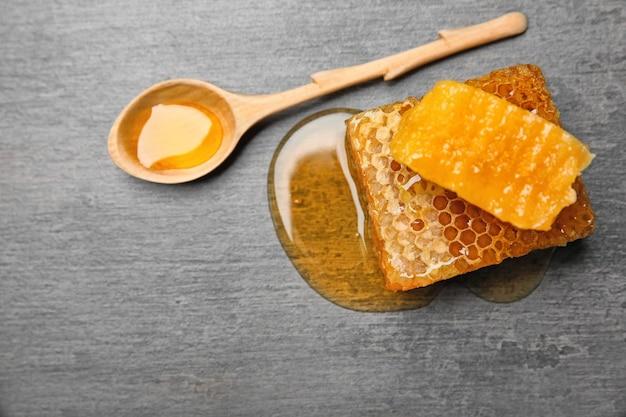 Свежие соты и деревянной ложкой с медом на сером фоне
