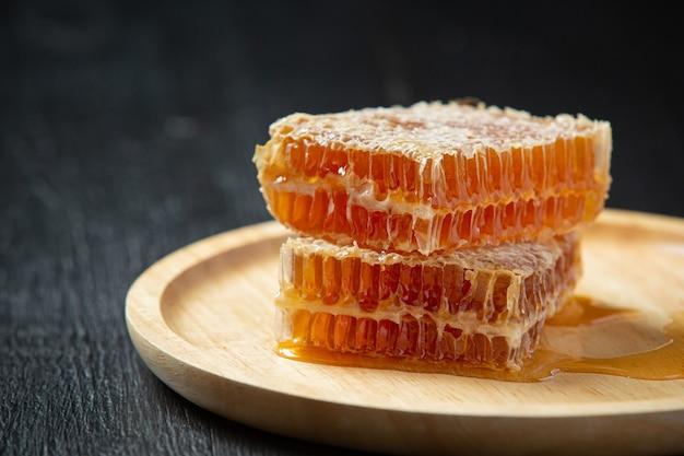 Fresh honeycombs on dark wooden surface
