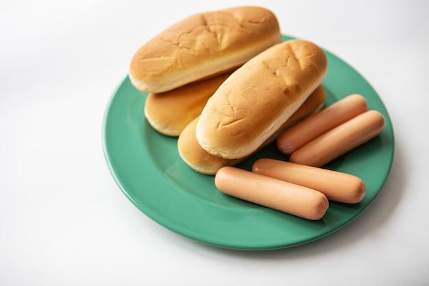 ソーセージと一緒に緑のプレートに横たわる新鮮なホットドッグのパン