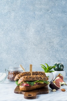 Fresh hot dogs on wooden board with jar of chilli flakes; potted plant fig slices and almonds