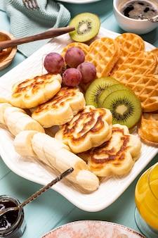 ターコイズブルーの表面にワッフルハート、ベリージャム、フルーツが入った新鮮な温かい花のパンケーキ。健康食品のコンセプト