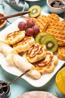 Fresh hot flowers pancakes with waffles hearts, berry jam and fruits on turquoise surface. healthy food concept