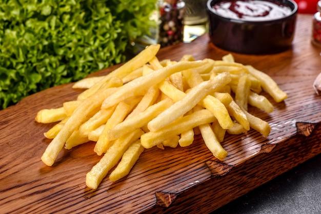 Свежий горячий картофель с солеными овощами и специями на темном бетонном фоне