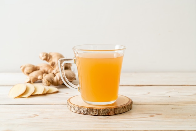 Fresh and hot ginger juice glass with ginger roots - healthy drink style