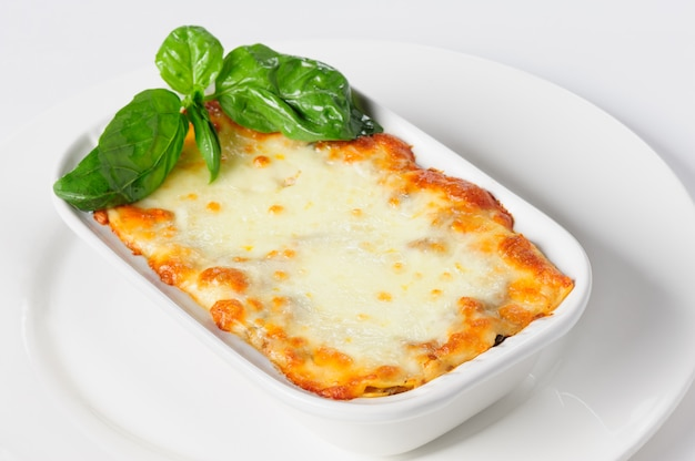 Fresh hot lasagna on white