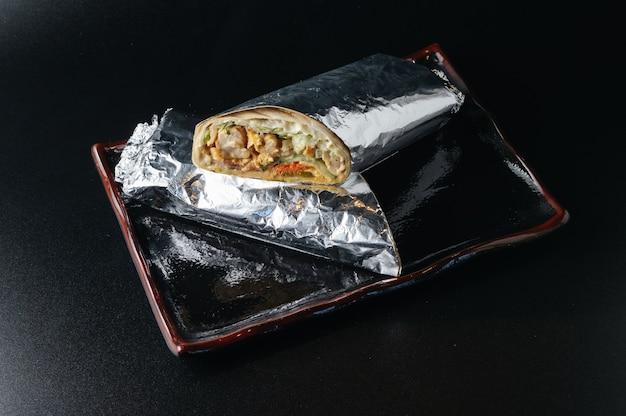 Свежая горячая шаурма из лаваша с мясом, завернутая в фольгу
