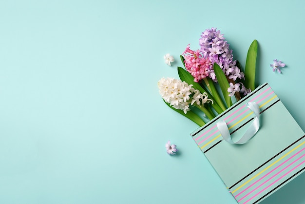 Fresh hyacinth flowers in shopping bag on blue punchy pastel background.