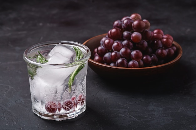 Fresh ice cold carbonated water in glass with rosemary leaf near to wooden bowl with grape berries, dark stone background, angle view