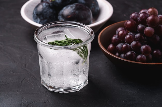 Fresh ice cold carbonated water in glass with rosemary leaf near to wooden bowls with grape and plum fruits, dark stone background, angle view