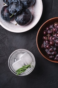 Fresh ice cold carbonated water in glass with rosemary leaf near to wooden bowls with grape and plum fruits, dark stone background, top view