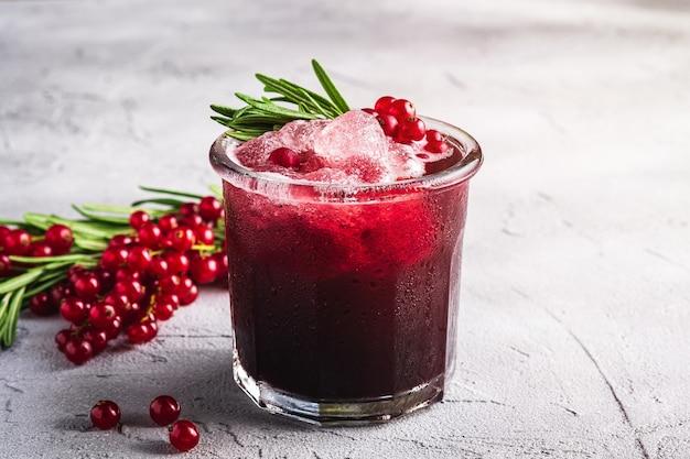 Свежий ледяной фруктовый коктейль в стекле, освежающий летний напиток из ягод красной смородины с листом розмарина на каменном бетонном фоне, угловой вид