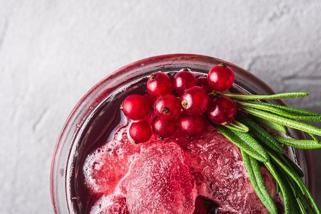 Свежий ледяной фруктовый коктейль в стекле, освежающий летний напиток из ягод красной смородины с листом розмарина на каменном бетонном фоне, макрос вид сверху