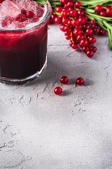 Свежий ледяной фруктовый коктейль в стекле, освежающий летний напиток из ягод красной смородины с листом розмарина на каменном бетонном столе, угол обзора копией пространства