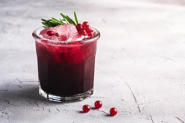 Свежий ледяной фруктовый коктейль в стакане, освежающий летний напиток из ягод красной смородины с листом розмарина