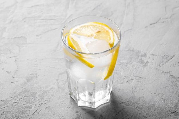 Свежий ледяной напиток с лимоном в стакане на бетонном фоне, вид ангела