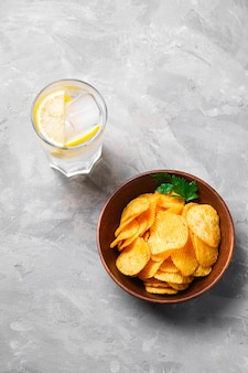 Свежий ледяной напиток с лимоном рядом с жареными гофрированными золотыми картофельными чипсами с листом петрушки в деревянной миске на бетонном фоне, вид ангела