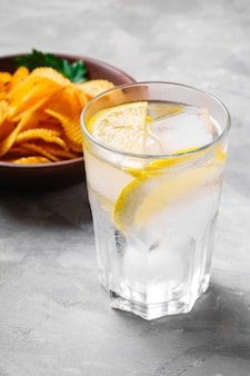 Свежий ледяной напиток с лимоном рядом с жареными гофрированными золотыми картофельными чипсами с листом петрушки в деревянной миске на бетонной стене, угловой вид