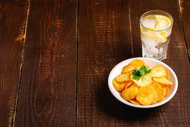 Свежий ледяной напиток с лимоном рядом с жареными картофельными чипсами с листом петрушки в деревянной миске на деревянном фоне, угол обзора копии пространства