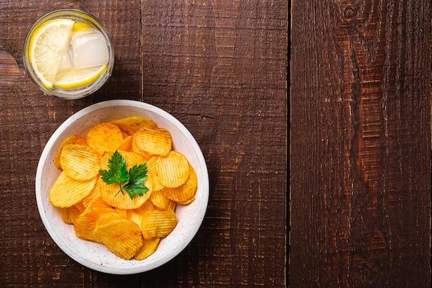 Свежий ледяной напиток с лимоном рядом с жареными картофельными чипсами с листом петрушки в деревянной миске на деревянном фоне, вид сверху копией пространства