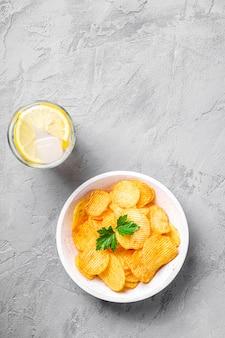 Свежий ледяной напиток с лимоном рядом с золотыми картофельными чипсами с листом петрушки в деревянной миске на бетонном фоне, вид сверху копией пространства