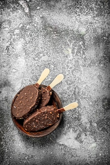 Fresh ice cream on a stick in chocolate with nuts on a rustic background