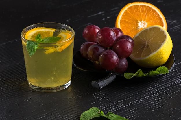 暗いテーブルにグレープフルーツのスライスと新鮮なアイスレモネード