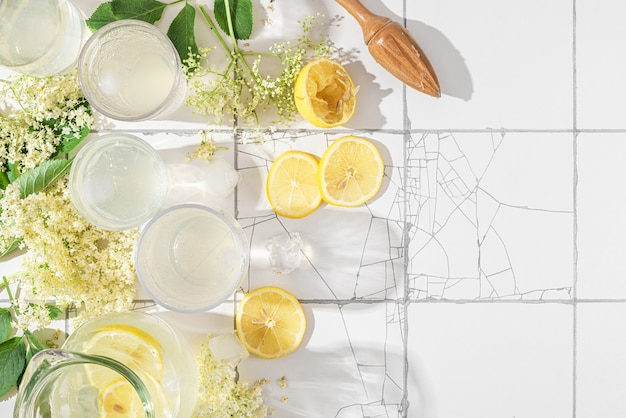 Свежий холодный безалкогольный коктейль или лимонад с лимонами и бузиной в очках на белом кафельном столе с копией пространства