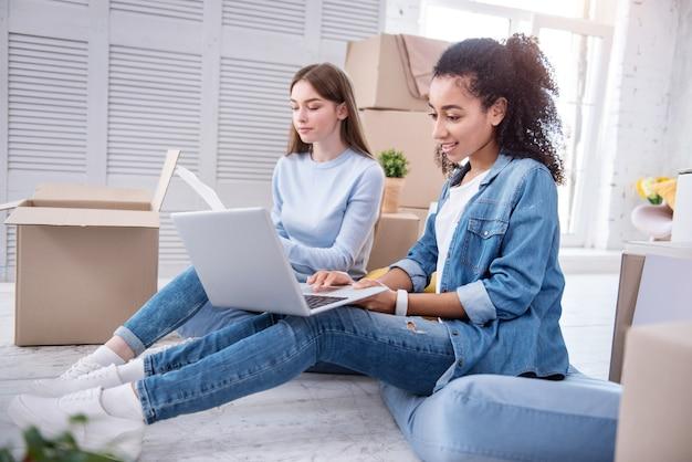 Свежие идеи. жизнерадостные студентки сидят на полу среди коробок с вещами и ищут идеи декора для своей новой общей квартиры.