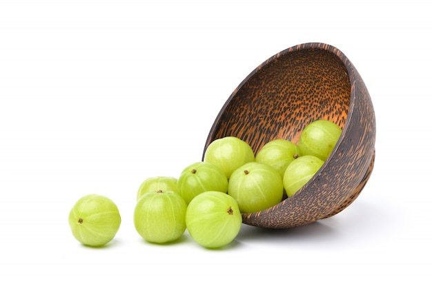 Fresh indian gooseberry fruits in wooden bowl on white.