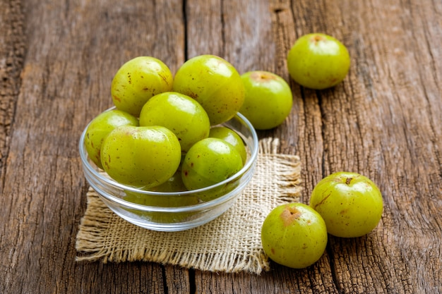 Fresh indian gooseberry in glass bowl  on wooden board