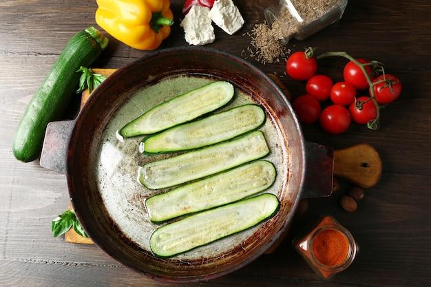 Свежие ингредиенты и жареные ломтики кабачков для приготовления рулетов из кабачков на деревянных