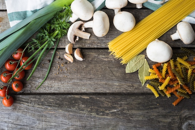 Fresh ingredients for cooking pasta, tomato and spices over wooden table background with copy space