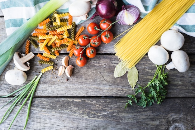 Fresh ingredients for cooking pasta, tomato and spices over wooden table with copy space