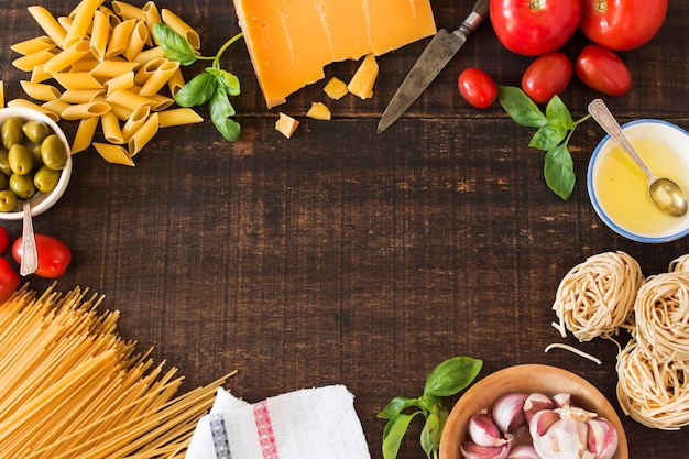 Fresh ingredients for cooking pasta on wooden background