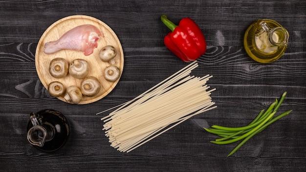 黒の素朴な木製テーブルで自家製焼きそばを調理するための新鮮な食材。上面図。