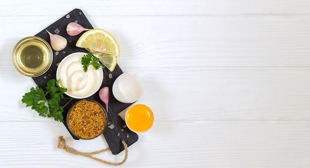 白い木製のテーブルトップビューでマヨネーズを調理するための新鮮な食材