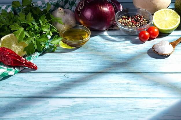 Свежие ингредиенты для приготовления пищи на синем деревянном столе с тенями, проходящими через окно кухни. с копией пространства.