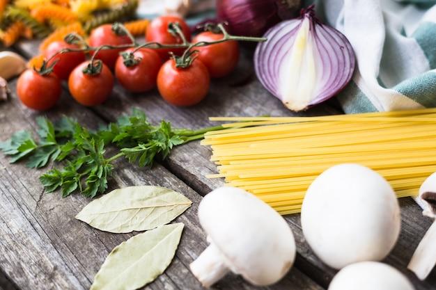 コピースペースのある木製のテーブルの上でパスタ、トマト、スパイスを調理するための新鮮な食材