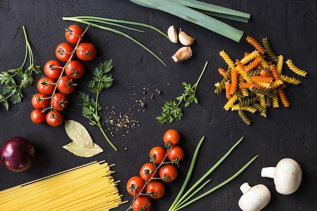 복사 공간 블랙 테이블에 파스타, 토마토, 양파, 마늘, 허브, 버섯, 향신료 요리를위한 신선한 재료