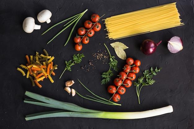 パスタ、トマト、玉ねぎ、ニンニク、ハーブを調理するための新鮮な食材