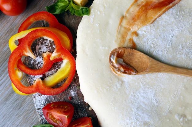 木製のテーブルでピザを準備するための新鮮な食材、クローズアップ