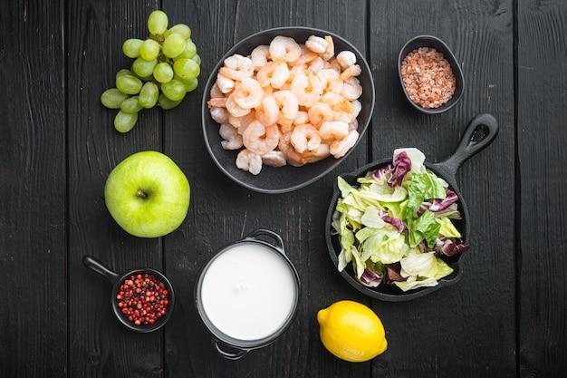 Свежие ингредиенты для вкусного салата из вальдорфских креветок, с яблочным соусом и виноградом, на черном деревянном столе, плоская планировка, вид сверху