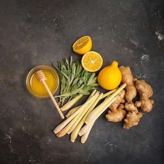 新鮮な食材ジンジャー、レモングラス、セージ、蜂蜜、レモンコピースペースと暗い背景に健康的な抗酸化物質と抗炎症ジンジャーティー。上面図。