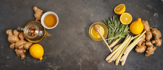 Fresh ingredients ginger, lemongrass, sage, honey and lemon for healthy antioxidant and anti-inflammatory ginger tea on dark background with copy space. top view.