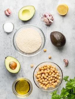 Fresh ingredients for healthy food hummus , cheak peas, avocado, olive oil, garlic cloves, sesame, salt, lemon and green parsley. top view, flat layout