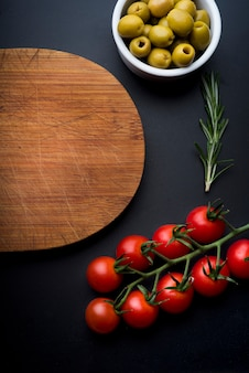 Fresh ingredients and wooden chopping board on kitchen counter