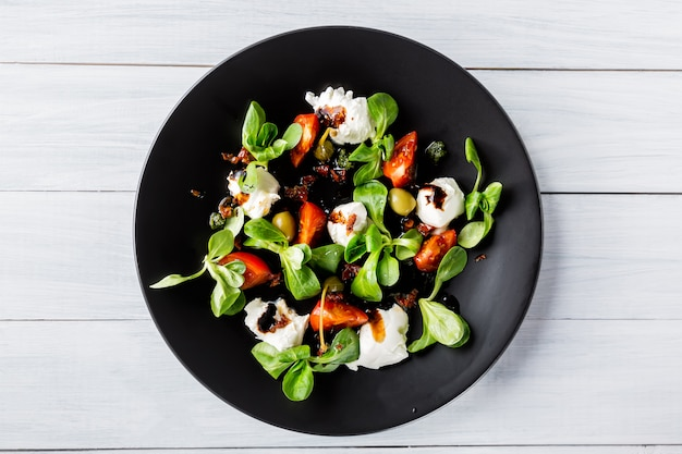 Fresh italian caprese salad with mozzarella and tomatoes on dark plate on white wooden table.